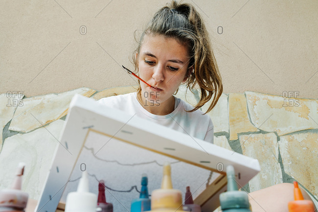 Caucasian girl biting a brush while painting with her finger