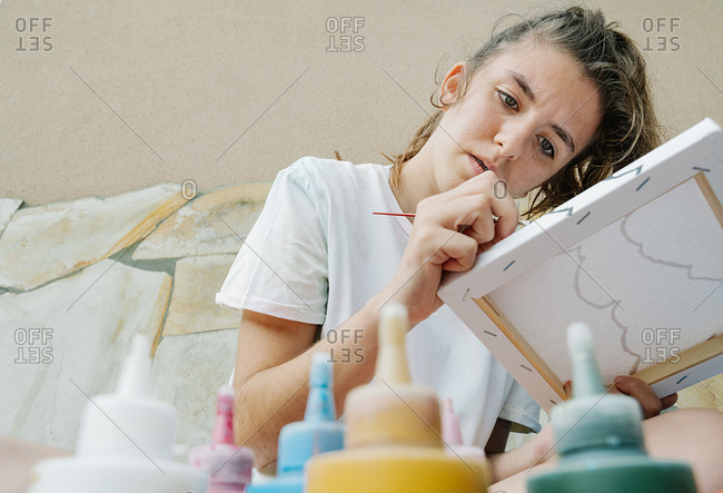 Caucasian girl painting with a brush, close up