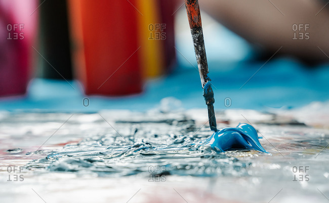Brush taking a blue paint from a painting palette