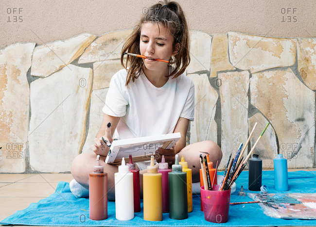 Caucasian girl biting a painting brush while painting with her finger, sitting on her terrace
