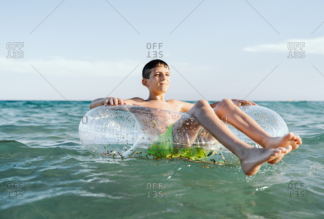 Relaxed Caucasian boy swimming in a float in the sea enjoying calm waves in summertime