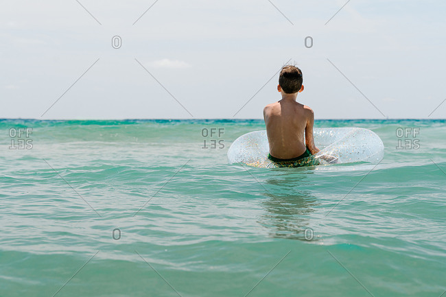 Relaxed Caucasian boy swimming in a float in the sea enjoying calm waves in summertime, back view