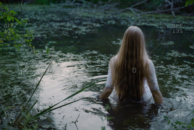 A woman in a white dress walks into a swamp.