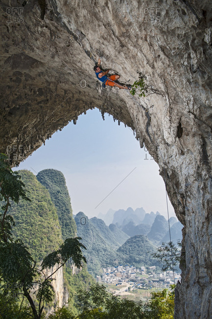 Man climbing on Moon Hill in Yangshuo, a climbing Mekka in China