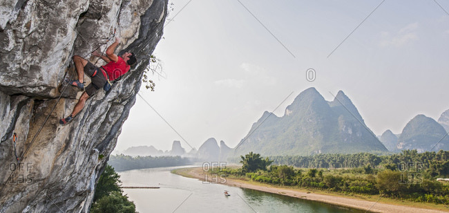 Man climbing at River Side in Yangshuo, a climbing Mekka in China