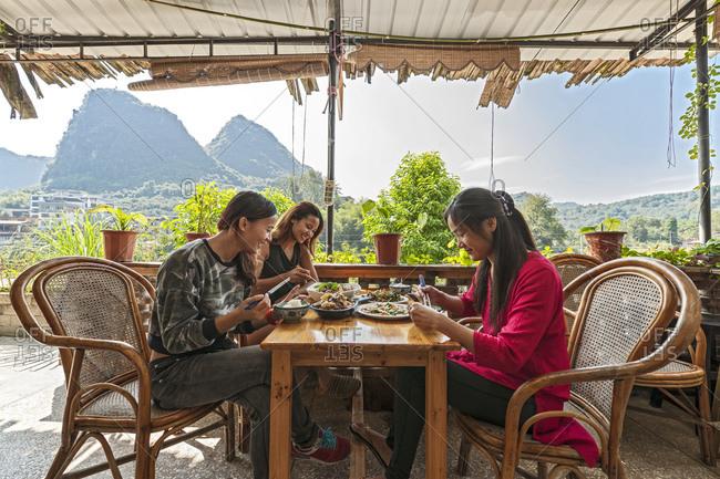 Three female friends having lunch on terrace