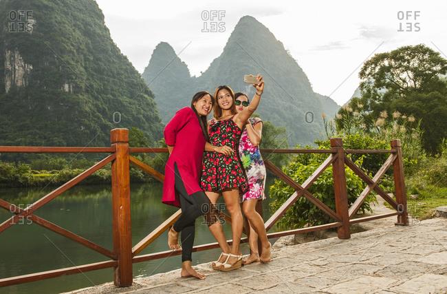 Three female friends taking selfie at river Li close to Yangshuo
