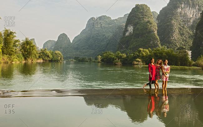 Three beautiful women standing in the river Li close to Yangshuo