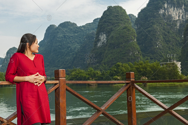 Beautiful woman resting her elbows on balustrade next to river Li