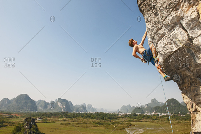Male climber pulling up on overhanging rock in Yangshuo / China