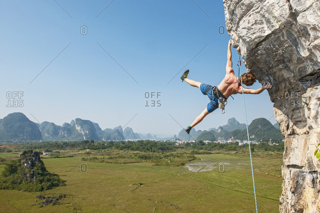 Male climber hanging sideways on overhanging rock in Yangshuo / China