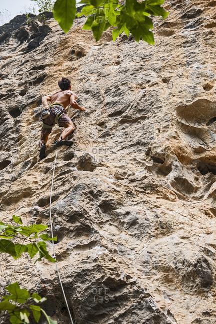 Man climbing limestone wall in Yangshuo / China