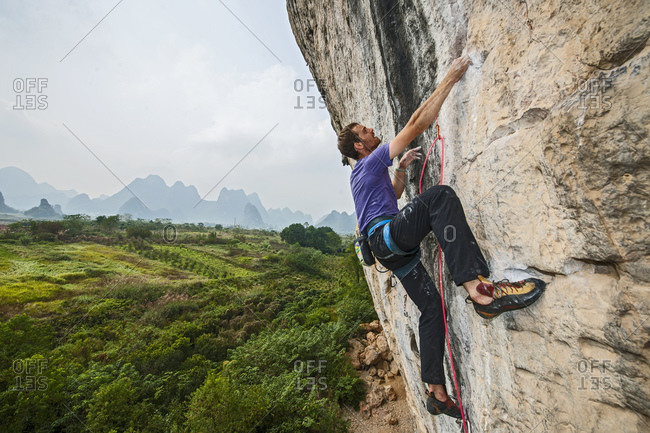 "Man climbing on the limestone cliff ""White Mountain"" in Yangshuo"