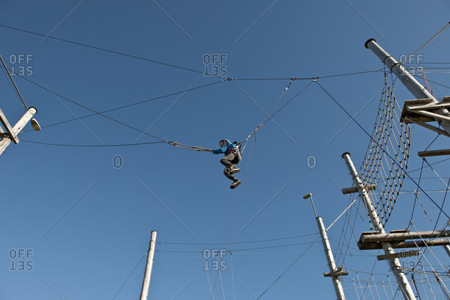 Boy on a high swing at high rope access course in Iceland