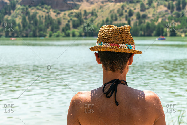 Woman in bathing suit contemplating the water, back view