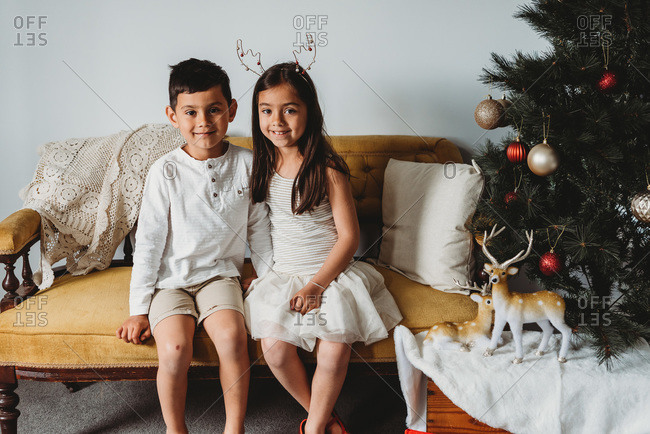 Multiracial young girl & boy sitting on couch next to Christmas decor