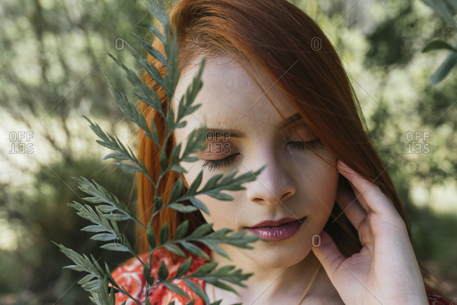 Portrait of a young woman with red hair, outdoors