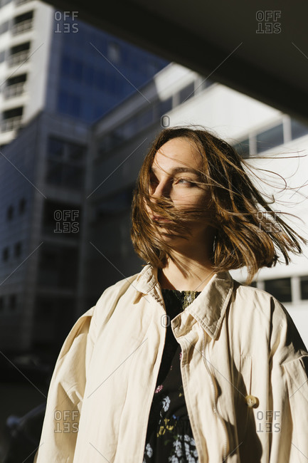 A woman in a raincoat walks around the city with her hair flying in the wind