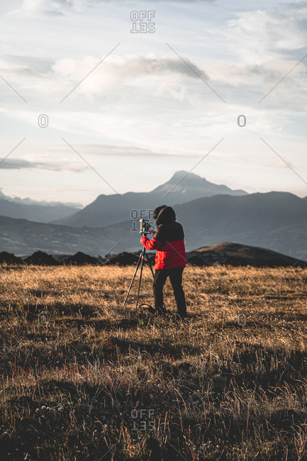 Photographer taking photos in the mountains with mountains behind