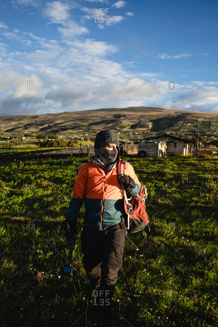 Young man walking in Andes mountains with sunset and equipment