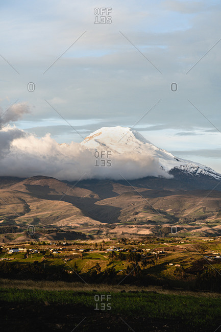 Cayambe mountain close up with sunlight and city