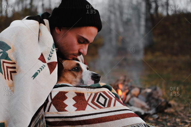 Man in poncho blanket by the camp fire hugs his dog, chilly autu