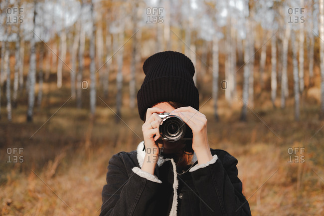 Portrait of a young woman with camera taking a picture in beautiful pose