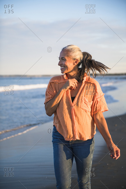 Gray Haired Woman enjoying the beach at sunset
