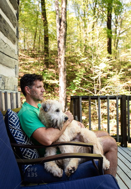 Man holding a fluffy dog on his lap outdoors on a deck in the woods.