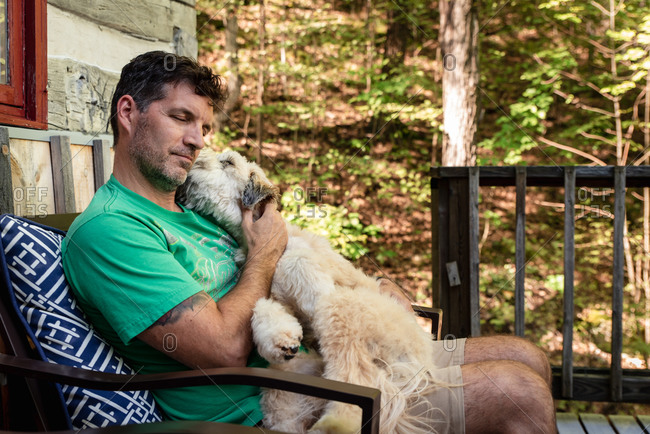 Man holding a fluffy dog on his lap outside on a deck in the woods.