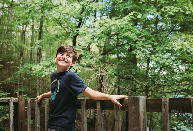 Happy young boy leaning against deck railing with trees in background.
