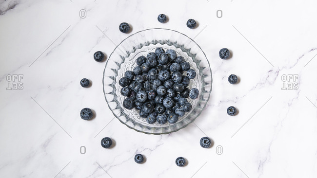 Group of blueberries in a glass dish on a marble table