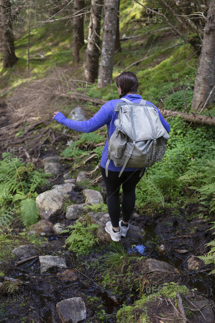 A girl tries to navigate a creek while hiking a trail in Norway