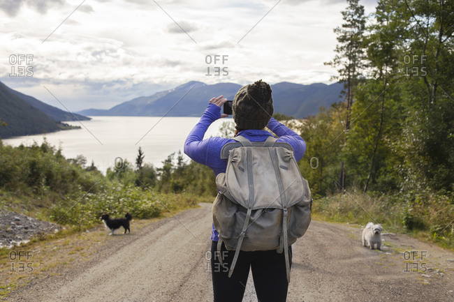 A young back packer taking a photo of the fjords in Norway