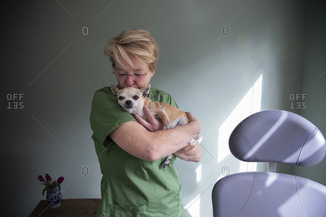 A medical worker holding and kissing her dog on the head