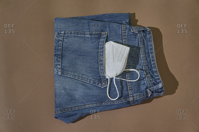 From above of folded jeans with white protective mask in pocket placed on brown background.