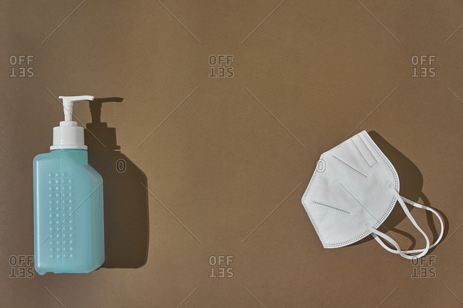 A protective mask against covid19 next to a disinfectant gel on a brown background