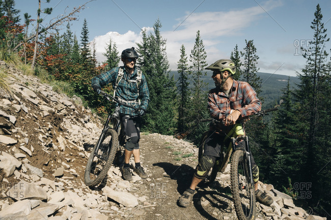 Two bikers take a break on the trail at the Timberline Bike park in OR