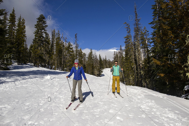 Two young women cross-country ski on Mt. Hood on a sunny day.