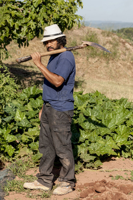 Portrait of a Colombian farmer, with a shovel.