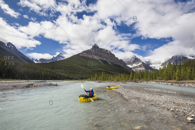 Adventurous man paddling on river in the Rocky Mountains, Alberta