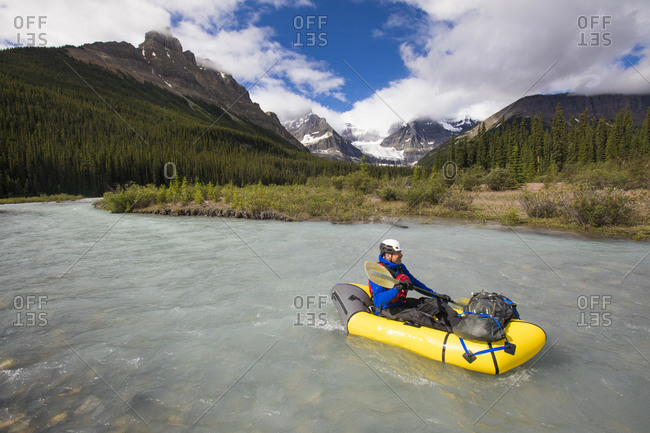High angle view of explorer navigating river in inflatable packraft.
