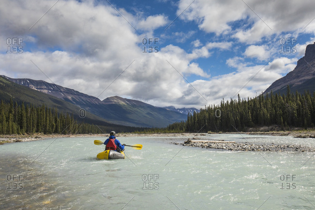 Rear view of person kayaking (Packrafting) in scenic valley, Banff.