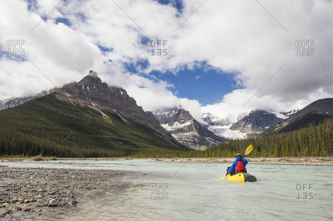 Man paddling on scenic river, Rocky mountains, Alberta, Canada.