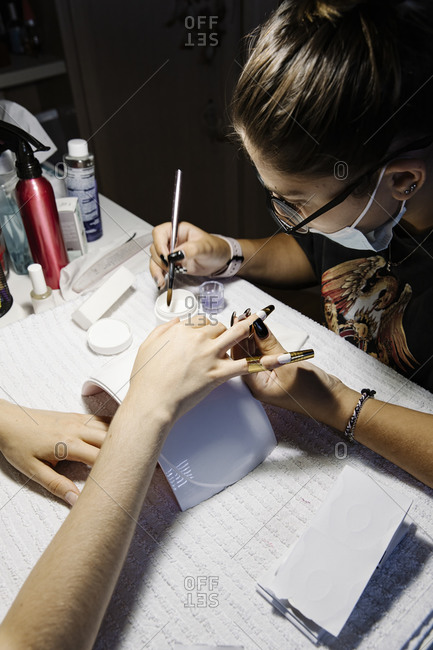 Woman in mask making French manicure to crop client during epidemic
