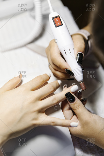 Crop stylist polishing nails of female client over table in salon