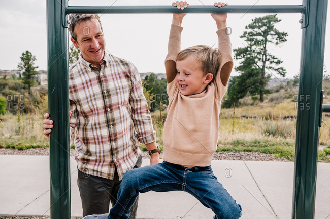 Young boy playing on a bar with his dad at a park
