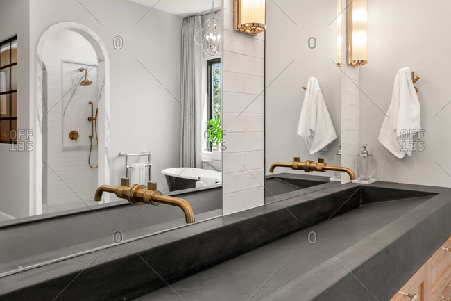Bathroom in luxury home with concrete sink and double vanity