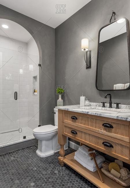 Bathroom in home with shower, vanity, mirror, sink, and tile floor