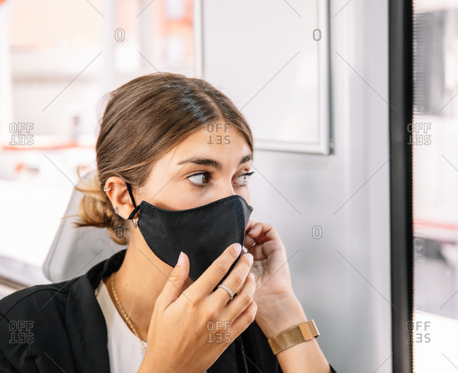 Female with pandemic mask talking on cell phone while commuting to work by train